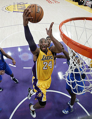 Los Angeles Lakers shooting guard Kobe Bryant (24) drives to the hoop to score against the Dallas Mavericks during their NBA basketball game on Tuesday