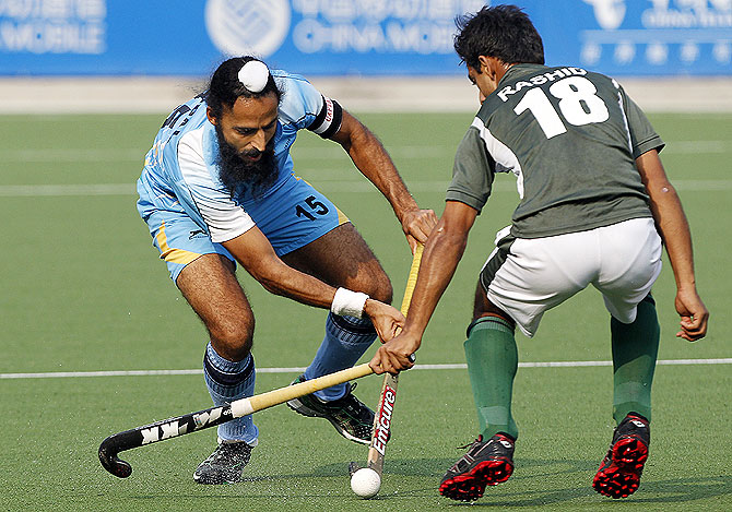 India's Singh Raj Pal (left) battles for the ball with Pakistan's Muhammad Rashid during their match at the 2010 Asian Games in Guangzhou, Guangdong