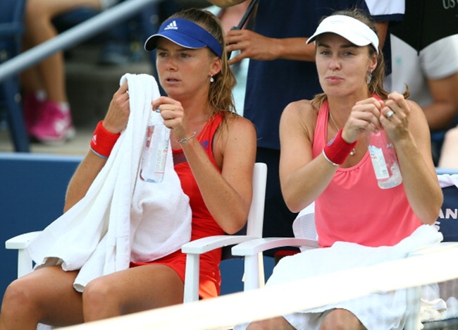 Martina Hingis of Switzerland talks with her partner Daniela Hantuchova of Slovakia during a break in their women's doubles first round match against Sara Errani of Italy and Roberta Vinci of Italy