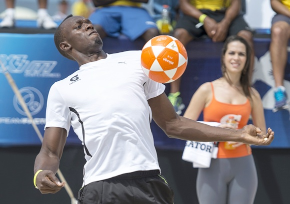Jamaican Olympic champion Usain Bolt plays footvolley, a combination of soccer and volleyball, one day before the Mano a Mano challenge on Copacabana beach in Rio de Janeiro