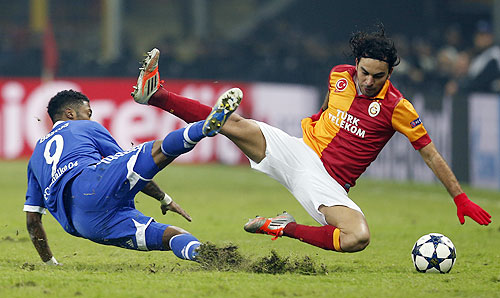 Galatasaray's Selcuk Inan (right) and Schalke 04's Michel Bastos (left) fall during a challenge in their Champions League match on Wednesday