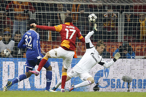Galatasaray's Burak Yilmaz (centre) scores past Schalke 04's goalkeeper Timo Hildebrand (right) and Joel Matip (left) during their Champions League match on Wednesday