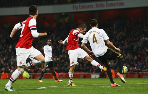 Jack Wilshere of Arsenal (centre) shoots past Chico Flores of Swansea City