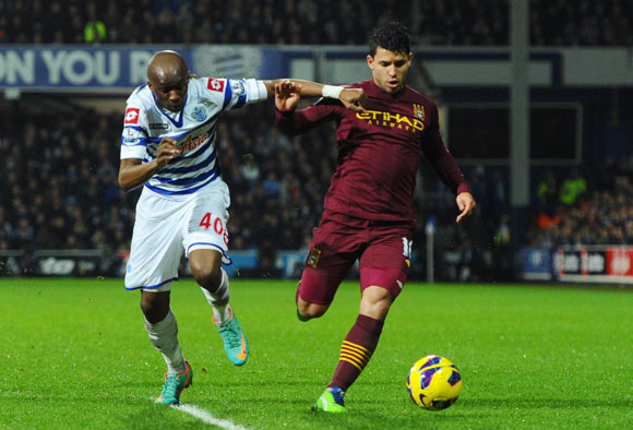 Sergio Arguero of Manchester City is pursued by Stephane Mbia of QPR during the Premier League match at Loftus Road