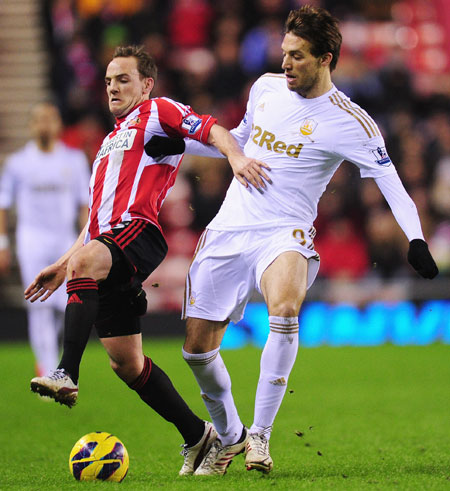 Swansea City player Michu (right) is challenged by Sunderland player David Vaughan during the Premier League match at Stadium of Light