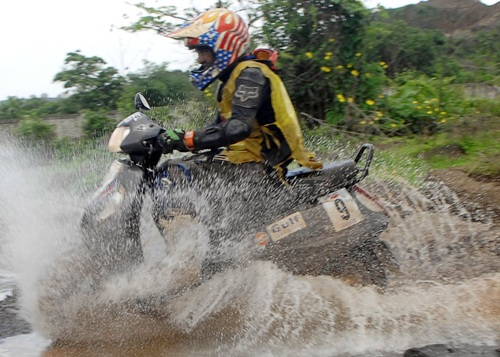 Muzaffar Ali negotiates a water-logged area during the Gulf Monsoon scooter rally