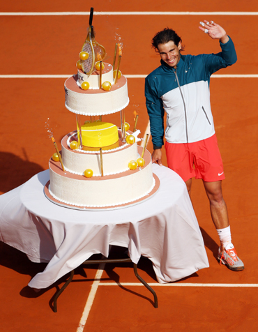Rafael Nadal of Spain waves to the crowd after being presented with a birthday cake following his victory over Kei Nishikori of Japan