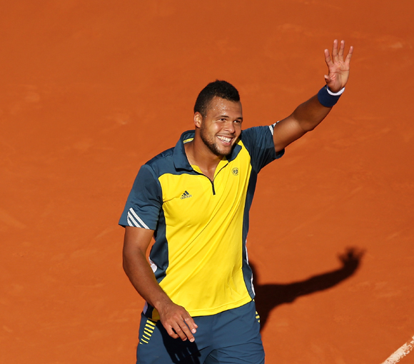 Jo-Wilfried Tsonga of France waves to crowd after victory against Roger Federer of Switzerland