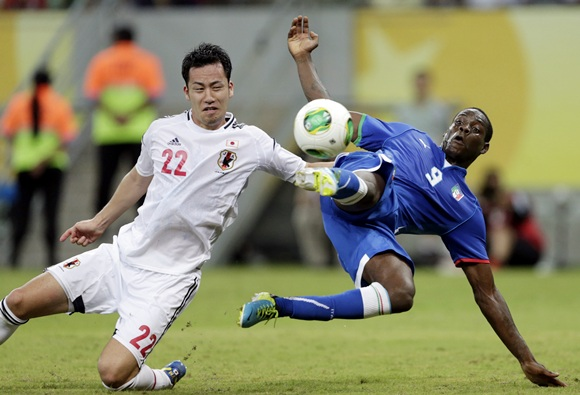 Italy's Mario Balotelli (right) attempts to score as Japan's Maya Yoshida challenges