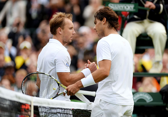 Steve Darcis of Belgium shakes hands at the net with Rafael Nadal of Spain after their first round match