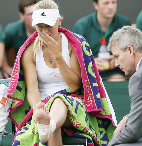 Caroline Wozniacki of Denmark reacts as she receives medical attention