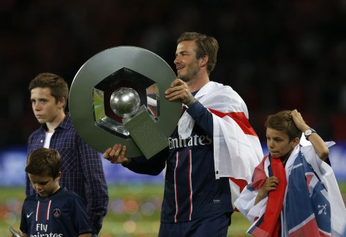 Paris Saint-Germain's David Beckham raises the French Championship trophy at the end of their team's French Ligue 1 soccer match