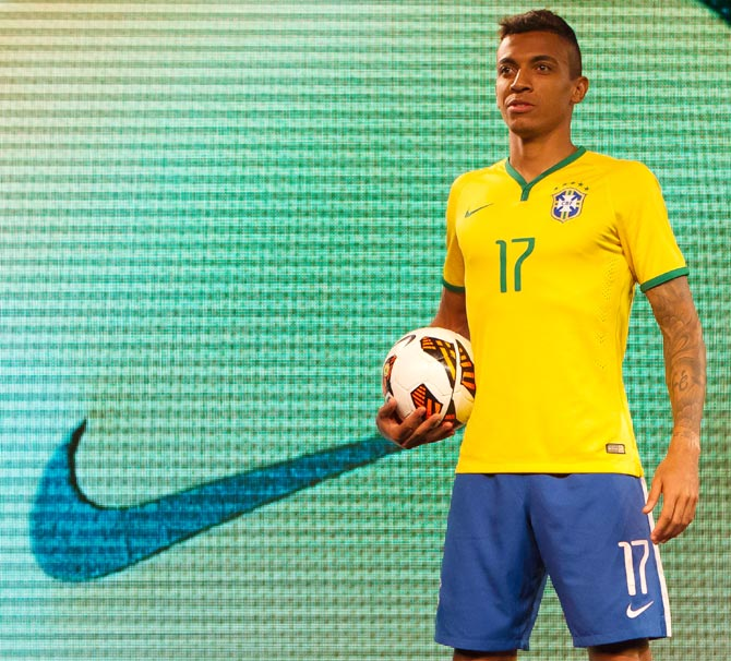 Luiz Gustavo poses with Brazil's new jersey for the 2014 FIFA World Cup