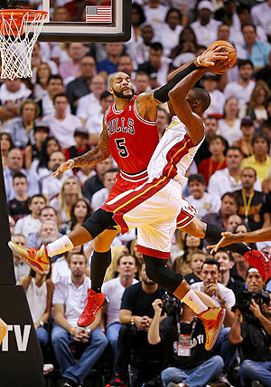 Carlos Boozer #5 of the Chicago Bulls blocks Chris Bosh #1 of the Miami Heat during a game at American Airlines Arena on Tuesday