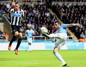 Alvaro Negredo (right) of Manchester City takes a shot as Mathieu Debuchy of Newcastle United takes evasive action during their League Cup Fourth Round match at St James' Park in Newcastle, England on Wednesday
