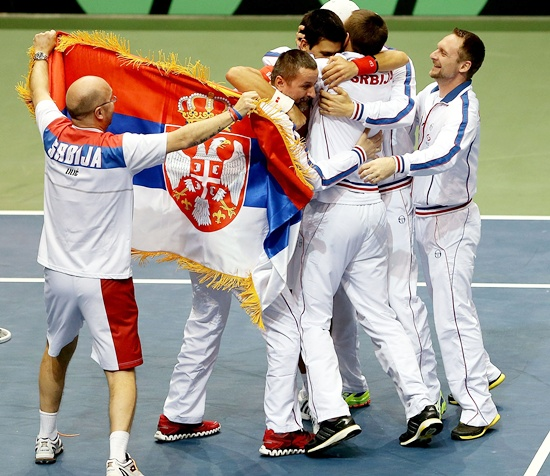 Novak Djokovic of Serbia celebrates his win in the fourth rubber against Sam Querrey with his teammates