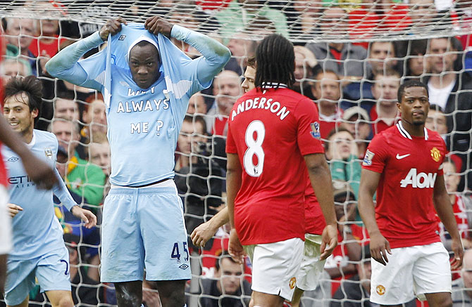 Mario Balotelli celebrates after scoring the opening goal for Manchester City against Manchester United in their English Premier League match at Old Trafford in  October 2011