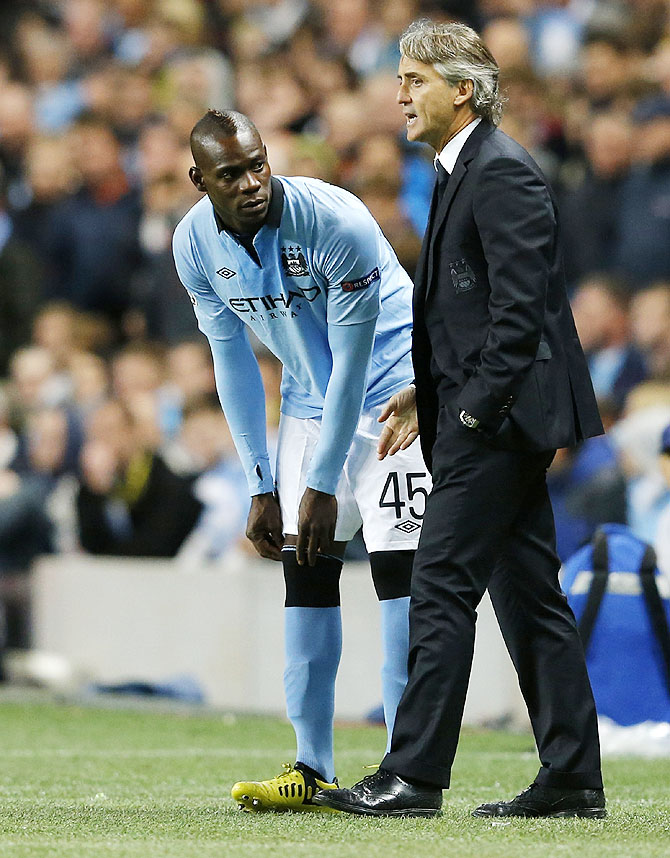 Mario Balotelli (left) with coach Roberto Mancini during his days with Manchester City