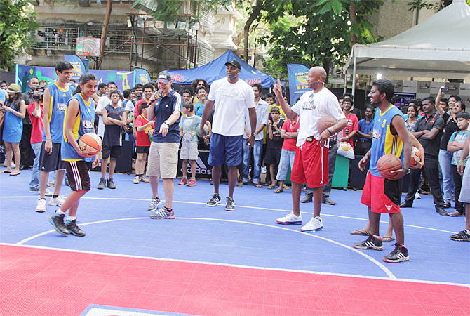 Peja Stojakovic shares shooting tips with a kid as Horace Grant, Ron Harper look on