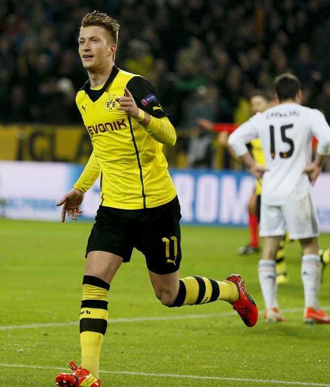 Borussia Dortmund's Marco Reus, left, celebrates after scoring a goal against Real Madrid