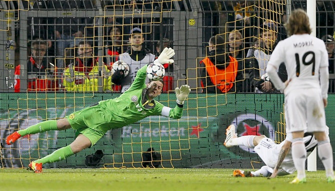 Borussia Dortmund's goalkeeper Roman Weidenfeller saves a penalty shot by Real Madrid's Angel di Maria (second right, covered)