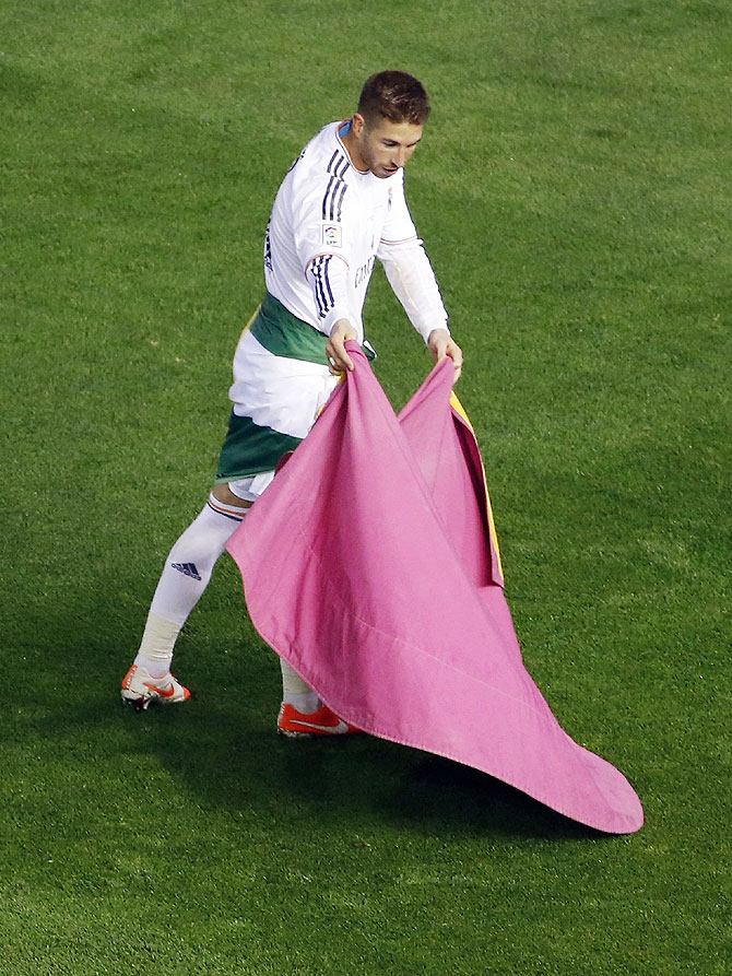 Real Madrid's Sergio Ramos uses a bullfighter's cape as he celebrates their win against Barcelona at the end their King's Cup final on Wednesday