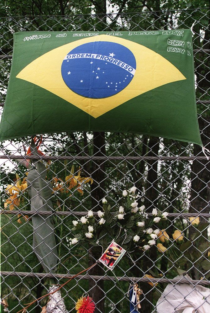 Flowers and mementos line the fencing as a tribute on the corner of the track where Ayrton Senna had crashed at Imola