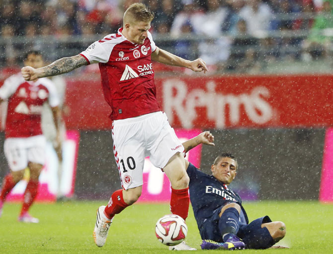 Quentin Pereira (left) of Stade Reims fights for the ball with Marco Verrati of Paris St Germain during their French Ligue 1 soccer match at the Gustave Delaune Stadium in Reims on Friday