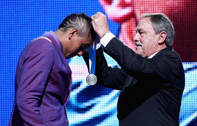 Australian tennis player Nick Kyrgios is presented with the Newcombe Medal by John Newcombe at the 2014 Newcombe Medal Awards at Crown Palladium in Melbourne on November 24