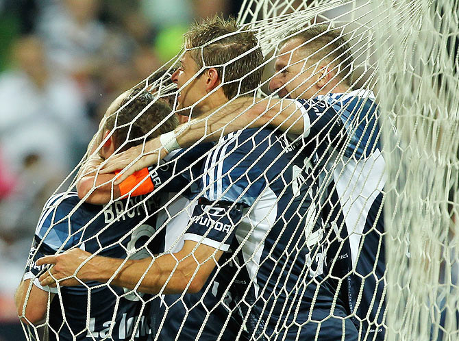 Leigh Broxham of Melbourne Victory celebrates with teammates after scoring against Adelaide United during the round eight A-League match at AAMI Park in Melbourne on November 28