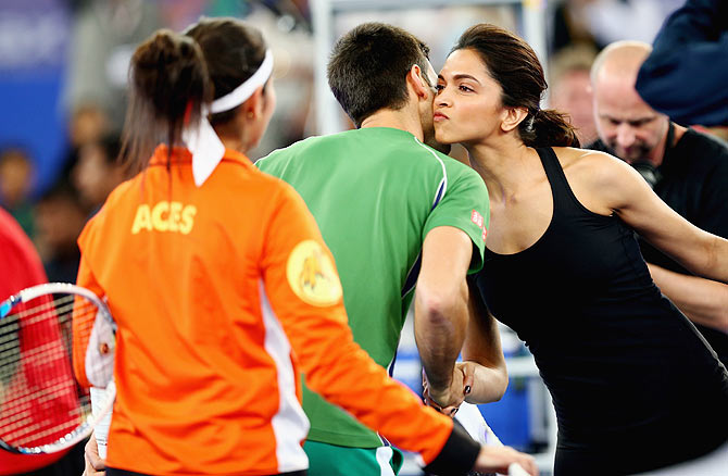 Deepika Padukone kisses Novak Djokovic of the UAE Royals during the International Premier Tennis League third leg at the Indira Gandhi Indoor Stadium on Monday