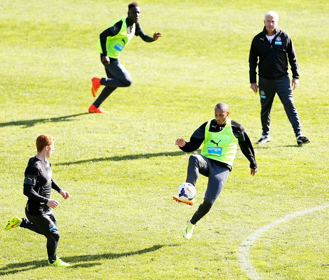 Yoan Gouffran controls the ball while manager Alan Pardew looks on during a Newcastle United   training session