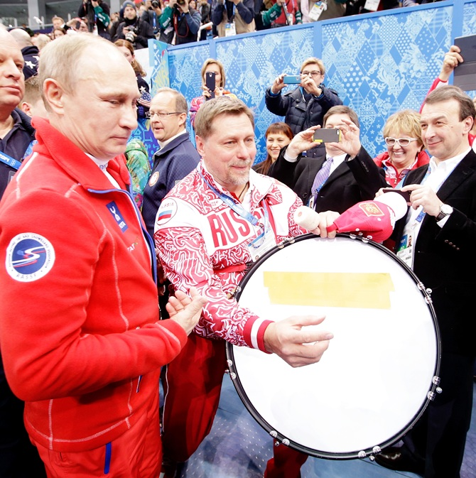 Russian President Vladimir Putin walks through the arena after the Flower Ceremony for the Team Figure Skating.