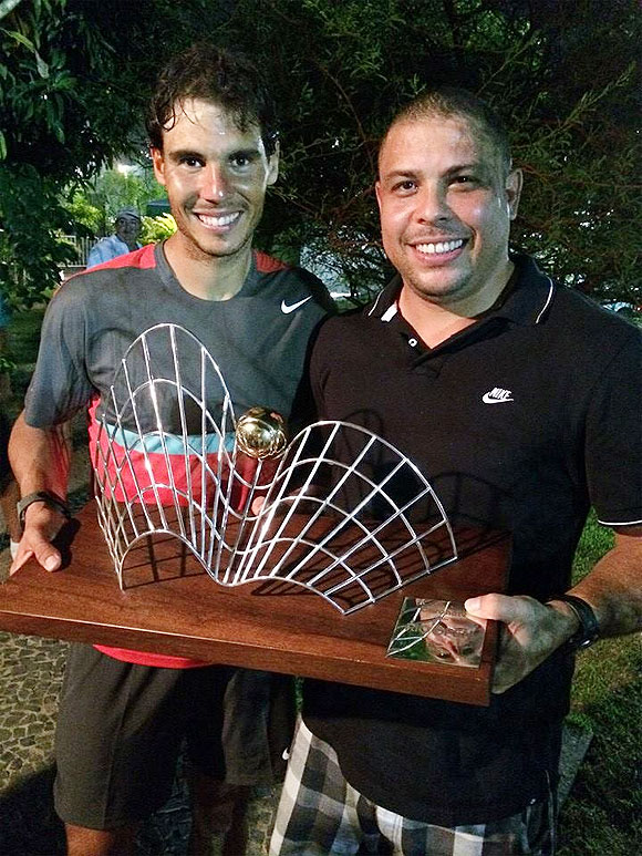 Rafael Nadal receives the trophy from former Brazil footballer Ronaldo after winning the Rio Open on Sunday