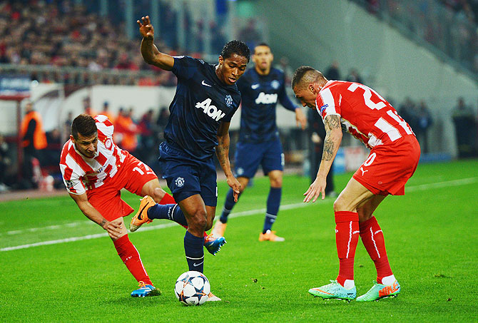 Jose Holebas (right) and Hernan Perez (left) of Olympiacos challenge Antonio Valencia (centre) of Manchester United during their UEFA Champions League match on Tuesday