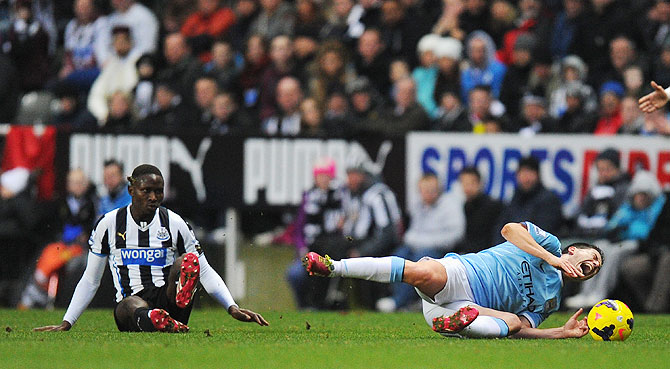 Newcastle player Mapou Yanga-Mbiwa (left) fouls Samir Nasri who was later stretchered off on Sunday