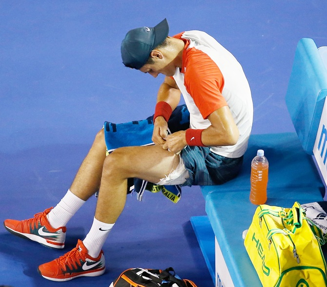 Bernard Tomic of Australia removes strapping from his leg