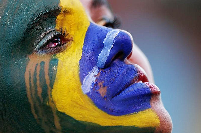 A Brazil fan cries as she watches the 2014 World Cup semi-final between Brazil and Germany at a fan area in Brasilia on Tuesday