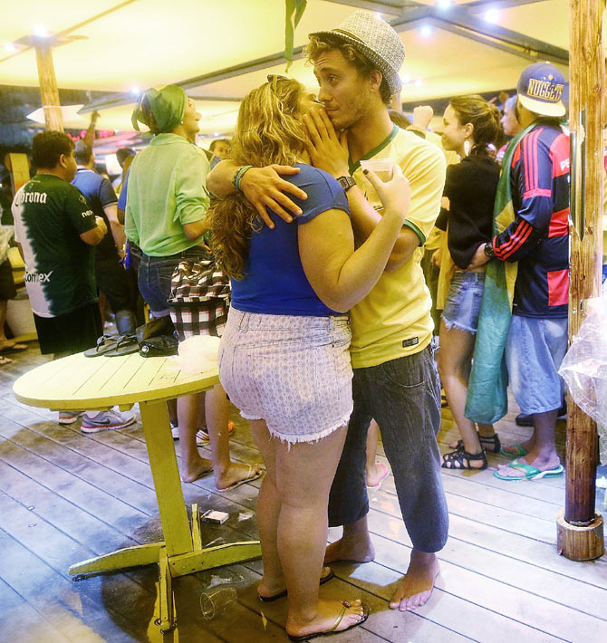 A Brazil fan is embraced by a woman in a bar on Copacabana Beach following the 2014 FIFA World Cup semi-final match between Brazil and Germany in Rio de Janeiro on Tuesday