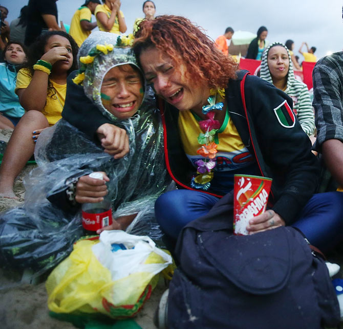Brazil fans are devastated while watching the first half on Copacabana Beach during the 2014 FIFA World Cup semi-final match between Brazil and Germany in Rio de Janeiro on Tuesday