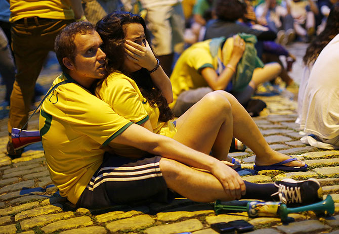 Brazil fans react as they watch their 2014 World Cup semi-finals against Germany on a street in Rio de Janeiro on Tuesday