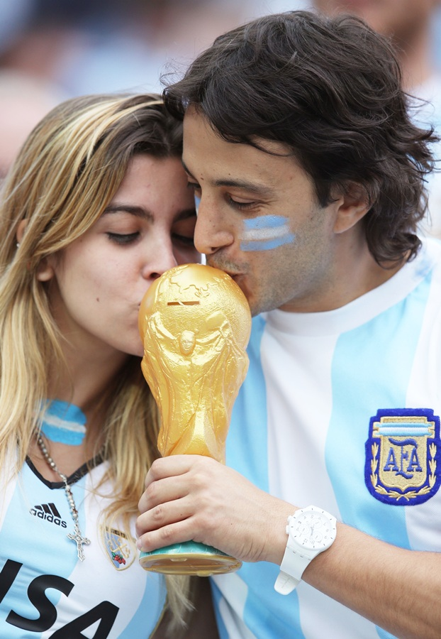 Argentina fans kiss a replica of the World Cup trophy