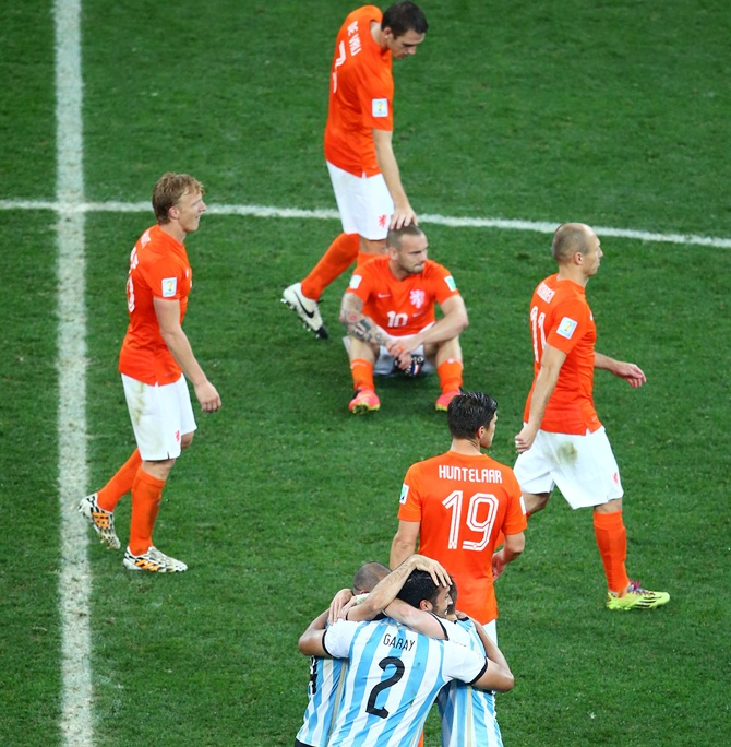 Javier Mascherano, Ezequiel Garay and Lucas Biglia of Argentina celebrate after   defeating the Netherlands in a penalty shootout as Dirk Kuyt, Stefan de Vrij,   Wesley Sneijder, Klaas-Jan Huntelaar and Arjen Robben of the Netherlands look on