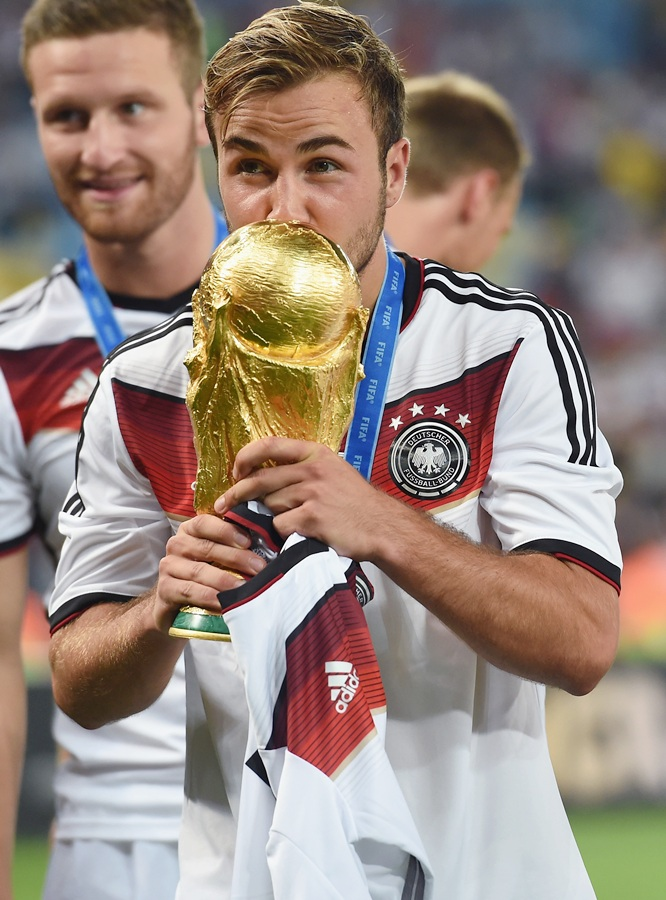 Mario Goetze of Germany kisses the World Cup trophy after defeating Argentina 1-0