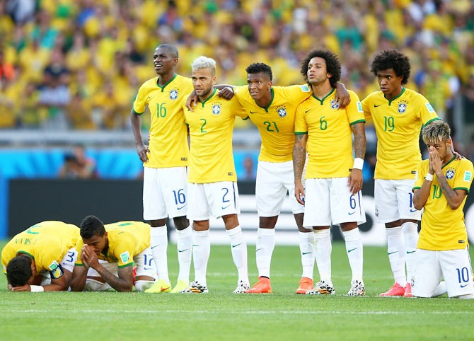 Thiago Silva, Luiz Gustavo, Ramires, Dani Alves, Jo, Marcelo, Hulk, Willian and   Neymar of Brazil look on during a penalty shootout against Chile
