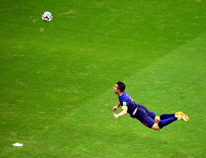 Robin van Persie of the Netherlands scores the team's first goal with a diving header against Spain in Salvador