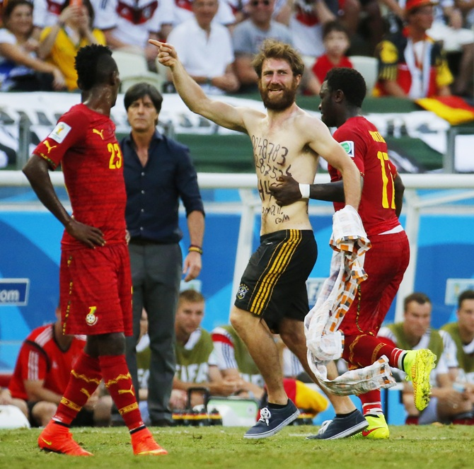 A pitch invader is escorted away by Ghana's Mohammed Rabiu, right, as teammate Harrison Afful watches during their 2014 World Cup Group G soccer match against Germany at the Castelao arena in Fortaleza