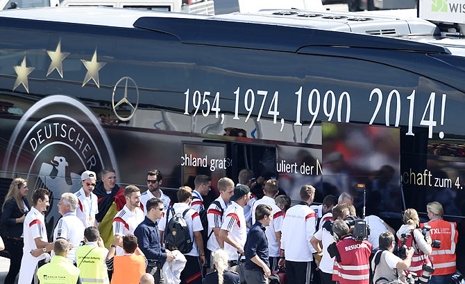 Germany's national soccer team players, winners of the 2014 World Cup, board a bus after their arrival at Tegel airport in Berlin