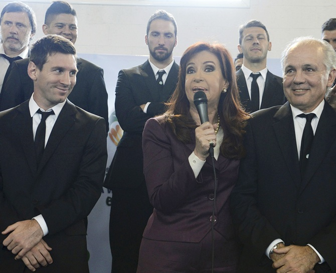 Argentine President Cristina Fernandez de Kirchner, centre, speaks next to Lionel Messi, left, and coach Alejandro Sabella