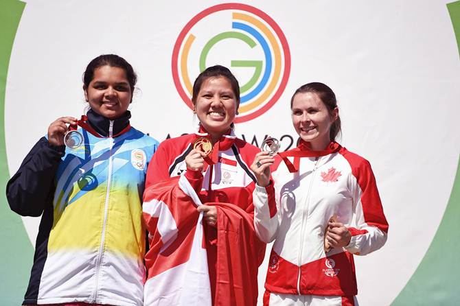 Shun Xie Tao of Singapore (centre), India's Malaika Goel (left) and Dorothy Ludwig of Canada display their medals after the women's 10 metre air pistol event at the Barry Buddon Shooting Centre on Day 2 if the Glasgow 2014 Commonwealth Games